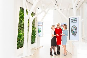 Three female employees are talking about sustainability in the Henkel Global Experience Center.